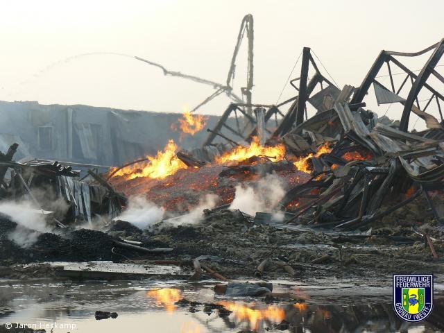 Lagerhalle mit 10.000 Tonnen Grillkohle steht in Flammen